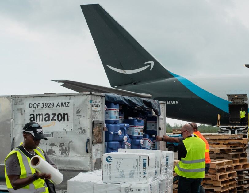 Workers on an airport tarmac with a cargo plane in the background. The plane has the Amazon smile logo on its tail.